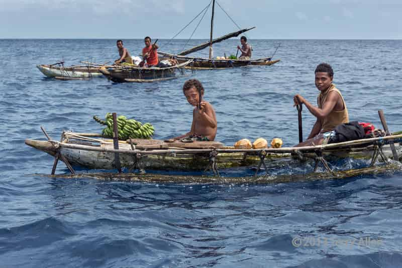 Boys in outrigger canoe selling coconuts